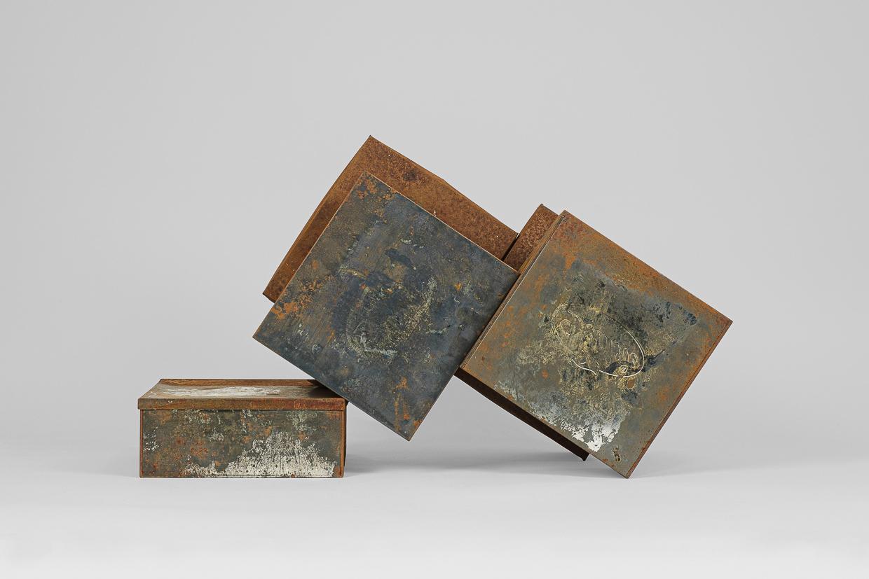 Photographie de Michel Rey prise de face. Elle représente 5 boîtes métalliques rouillées agencées en équilibre instable.