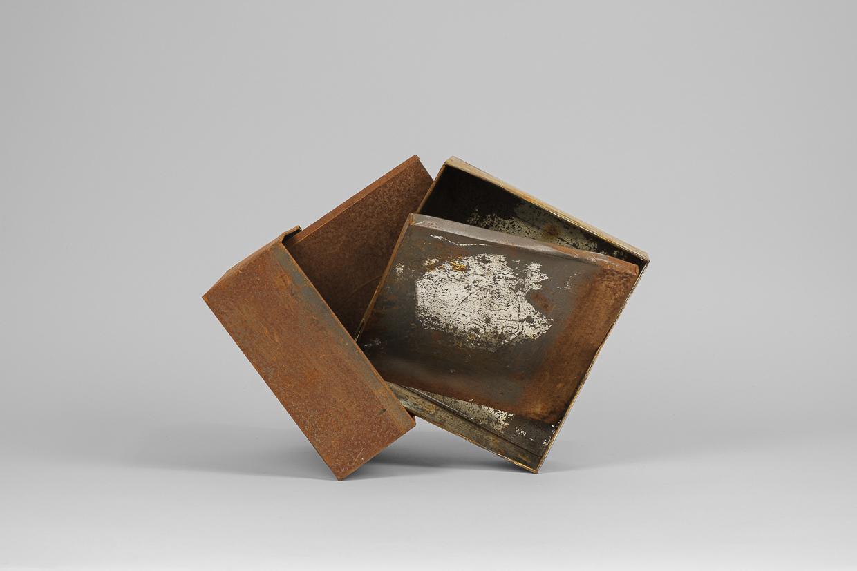 Photographie de Michel Rey prise de face. Elle représente 2 boîtes métalliques rouillées agencées en équilibre instable, les couverles séparées.