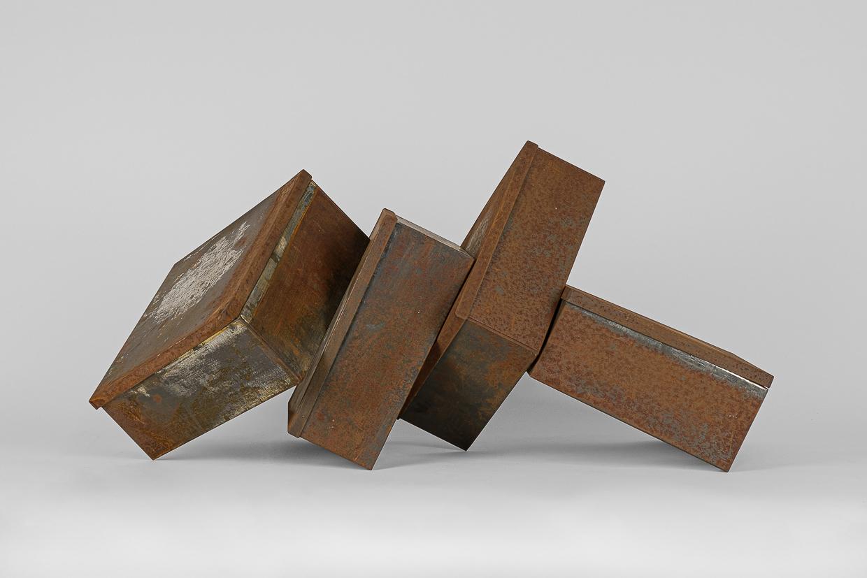 Photographie de Michel Rey prise de face. Elle représente 4 boîtes métalliques rouillées agencées en équilibre instable, les couverles légèrement entrouverts