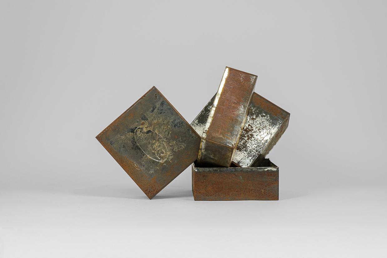 Photographie de Michel Rey prise de face. Elle représente 4 boîtes métalliques rouillées agencées en équilibre instable, .