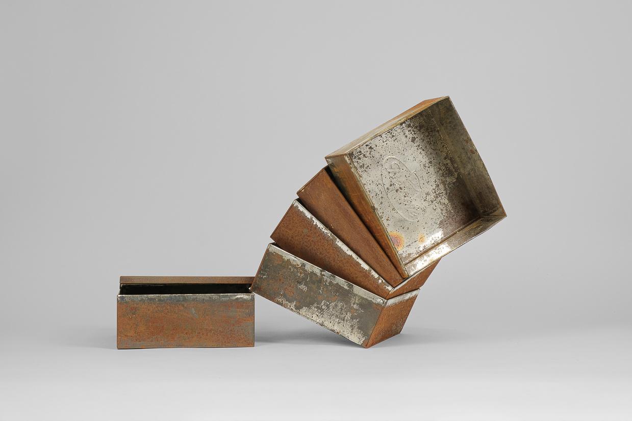 Photographie de Michel Rey prise de face. Elle représente 5 boîtes métalliques rouillés couverles enlevés et empilées en accordéon les une dans les autres.