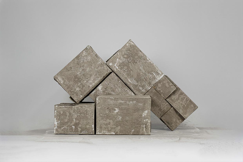 Photographie de Michel Rey prise de face. Elle représente 6 cartons usagés, peints avec de la cendre. Ils sont agencées en équilibre instable et empilés en oblique et horizontalement les uns sur les autres.