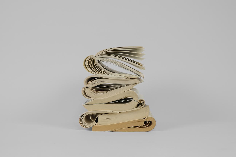 Photographie de Michel Rey prise de face. Elle représente 5 livres usagés, entrouverts. Ils sont agencés en équilibre instable, pliés en deux et empilés les uns sur les autres.