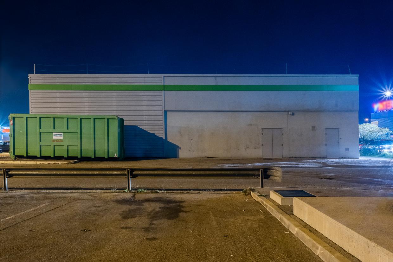 Photographie de Michel Rey prise au Centre Commerciale Plan de campagne situé entre Marseille et Aix-en-Provence..Les photographies sont prises de nuit. Elle représente une vue d'un bâtiment horizontal gris avec une benne verte devant