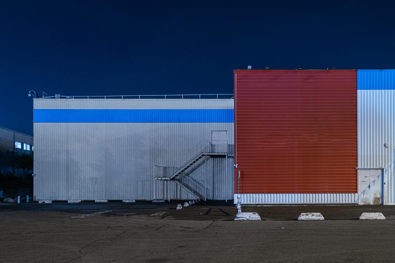 Photographie de Michel Rey prise au Centre Commerciale Plan de campagne situé entre Marseille et Aix-en-Provence..Les photographies sont prises de nuit. Elle représente une vue d'un bâtiment horizontal bleu et rouge avec un escalier métallique devant