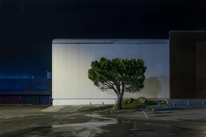 Photographie de Michel Rey prise au Centre Commerciale Plan de campagne situé entre Marseille et Aix-en-Provence..Les photographies sont prises de nuit. Elle représente une vue d'un bâtiment horizontal blanc avec un arbre devant