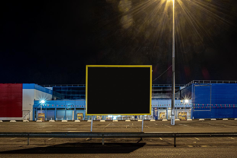 Photographie de Michel Rey prise au Centre Commerciale Plan de campagne situé entre Marseille et Aix-en-Provence..Les photographies sont prises de nuit. Elle représente une vue des bâtiments horizontaux bleus et rouges avec un panneau publicitaire noir sans affiche devant