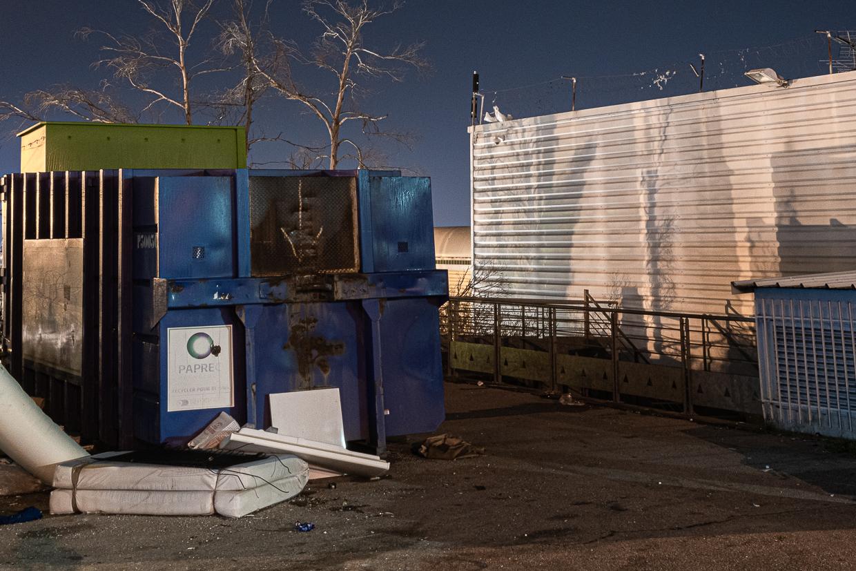 Photographie de Michel Rey prise au Centre Commerciale Plan de campagne situé entre Marseille et Aix-en-Provence..Les photographies sont prises de nuit. Elle représente une vue d'un batiment blanc avec un un poste transformateur électrique bleu et des détritus devant