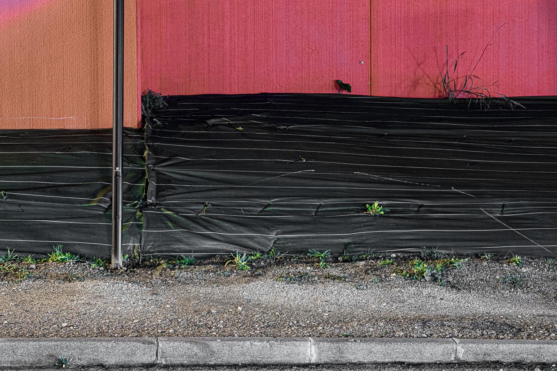 Photographie de Michel Rey prise au Centre Commerciale Plan de campagne situé entre Marseille et Aix-en-Provence..Les photographies sont prises de nuit. Elle représente une vue d'un batiment rouge avec des bandes de plastique noire accolées
