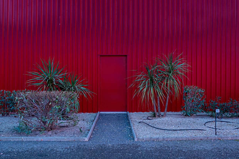 Photographie de Michel Rey prise au Centre Commerciale Plan de campagne situé entre Marseille et Aix-en-Provence..Les photographies sont prises de nuit. Elle représente une vue d'un batiment rouge avec une porte rouge et des arbustes devant