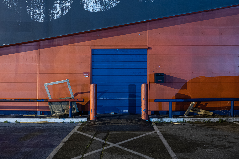 Photographie de Michel Rey prise au Centre Commerciale Plan de campagne situé entre Marseille et Aix-en-Provence..Les photographies sont prises de nuit. Elle représente une vue d'un batiment orange avec une porte bleue, des barrières et des encombrants devant