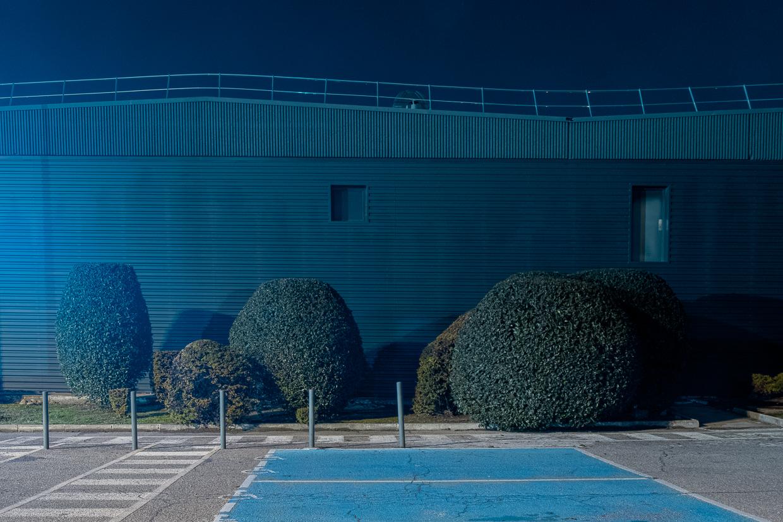 Photographie de Michel Rey prise au Centre Commerciale Plan de campagne situé entre Marseille et Aix-en-Provence..Les photographies sont prises de nuit. Elle représente une vue d'un batiment bleu avec des fenestrons bleus et des arbustes et des places de parking devant