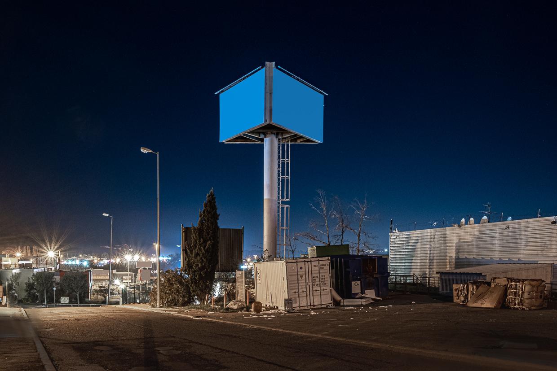 Photographie de Michel Rey prise au Centre Commerciale Plan de campagne situé entre Marseille et Aix-en-Provence..Les photographies sont prises de nuit. Elle représente une vue d'un batiment rbleu avec des fenestrons bleus et des arbustes et des places de parking devant