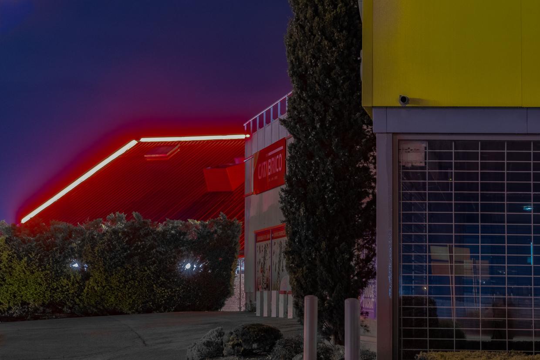 Photographie de Michel Rey prise au Centre Commerciale Plan de campagne situé entre Marseille et Aix-en-Provence..Les photographies sont prises de nuit. Elle représente une vue d'un batiment jaune éclairé par des néons rouges et un cyprè devant