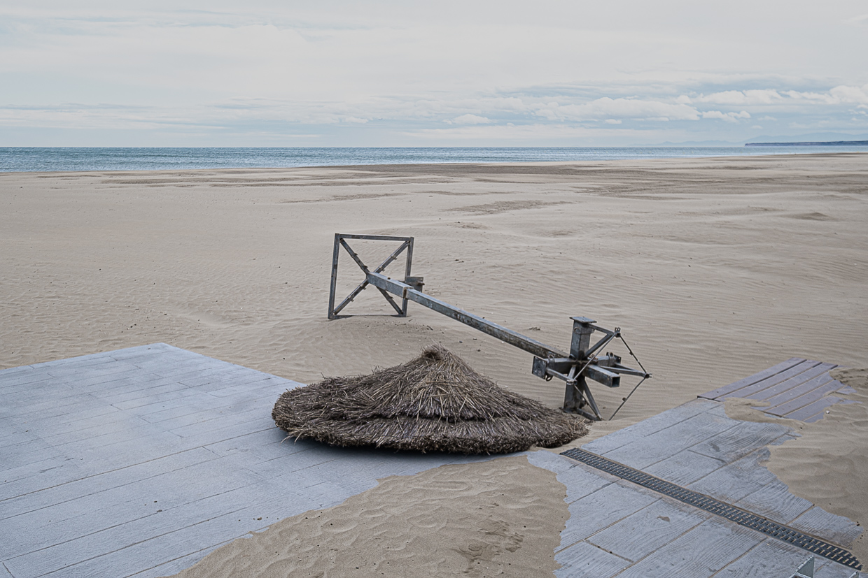 Photographie de Michel Rey prise à Port-La-Nouvelle dans l'Aude. Elle représente une vue de la plage avec unparasol en paille couché sur la plage