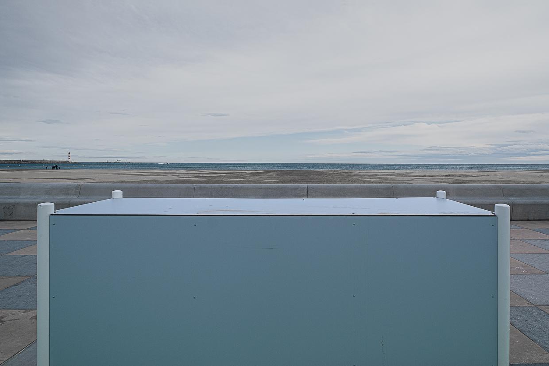 Photographie de Michel Rey prise à Port-La-Nouvelle dans l'Aude. Elle représente une vue de la plage avec une armoire électrique bleue en premier-plan