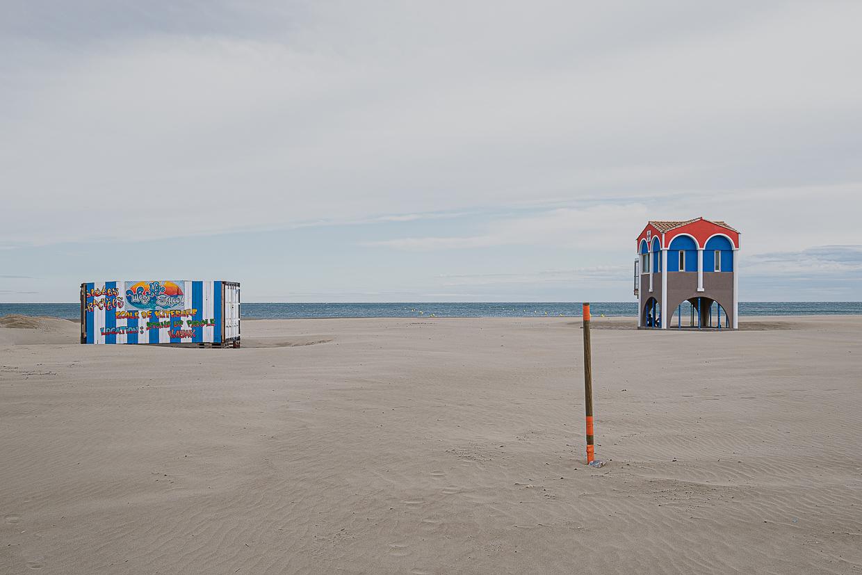 Photographie de Michel Rey prise à Port-La-Nouvelle dans l'Aude. Elle représente une vue de la plage avec un cabanon de sécurité, un bungalow de marcahnd de frites et un piquet orange en premier-plan