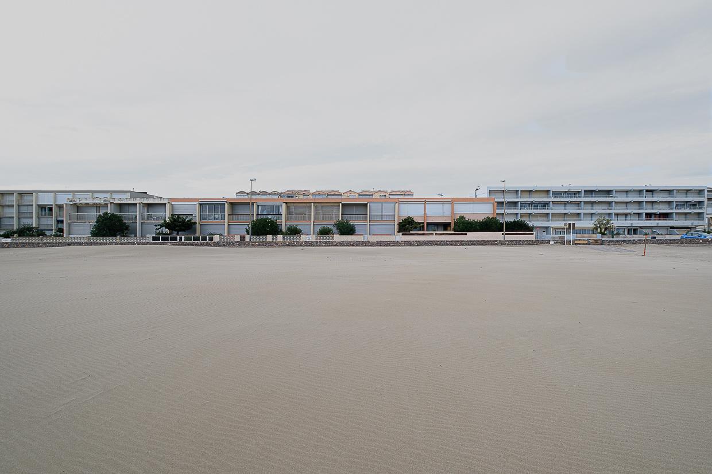 Photographie de Michel Rey prise à Port-La-Nouvelle dans l'Aude. Elle représente une vue prise de de la plage avec une barre d'immeuble donnant sur la plage en premier-plan