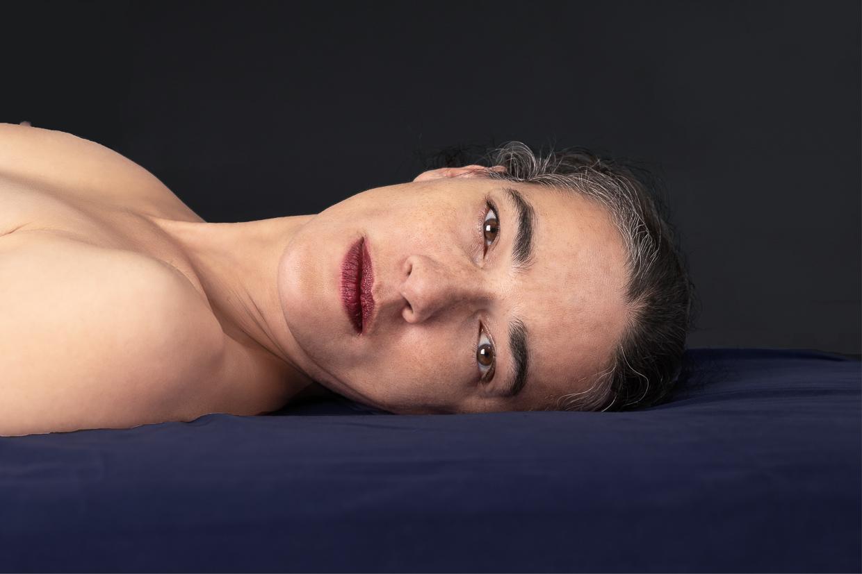Photographie de Michel Rey - Portrait d'une femme nus couchée, le regard fixé vers le spectateur