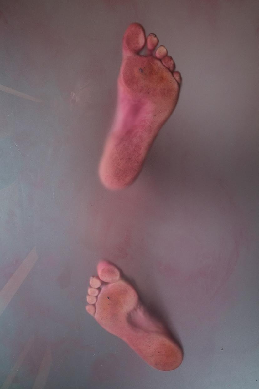 Photographie de Michel Rey prise en dessous d'une table vitrée. Elle représente les pieds d'une femme nue debout peinte partiellement en rouge
