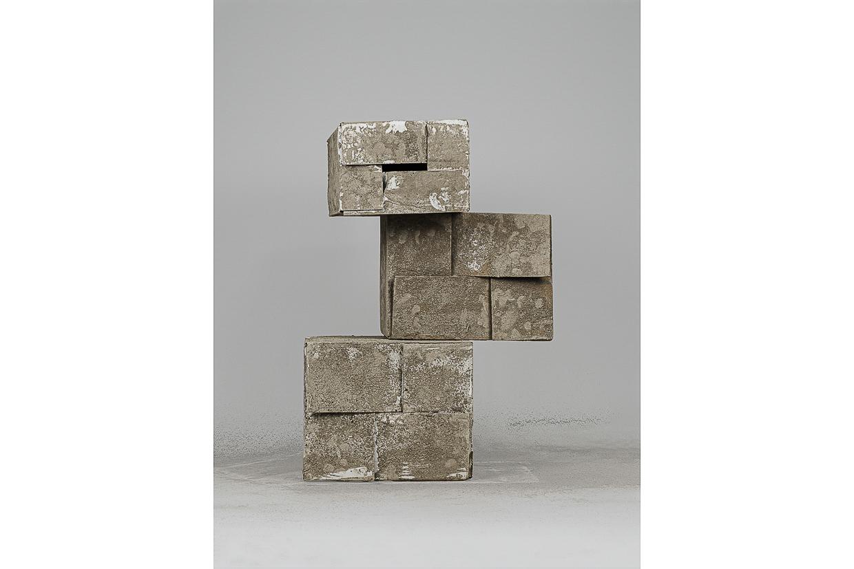 Photographie de Michel Rey prise de face. Elle représente 3 cartons usagés, peints avec de la cendre. Ils sont agencées en équilibre instable et empilées les uns sur les autres..