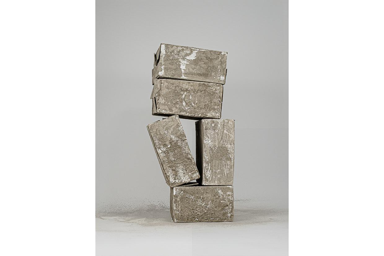 Photographie de Michel Rey prise de face. Elle représente 3 cartons usagés, peints avec de la cendre. Ils sont agencées en équilibre instable dont 2 sont empilés en V les uns sur les autres.