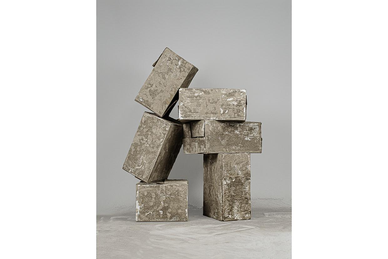 Photographie de Michel Rey prise de face. Elle représente 6 cartons usagés, peints avec de la cendre. Ils sont agencées en équilibre instable et empilés en deux colonnes les uns sur les autres.