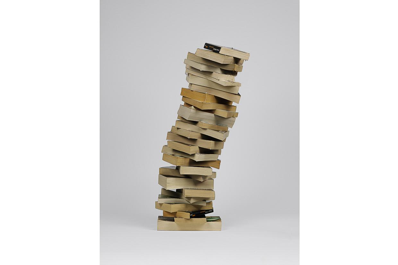 Photographie de Michel Rey prise de face Elle représente 28 livres usagés, jaunis, fermés. L'ensemble forme un colonne penchée. Ils sont agencés en équilibre instable, couchés les uns sur les autres.