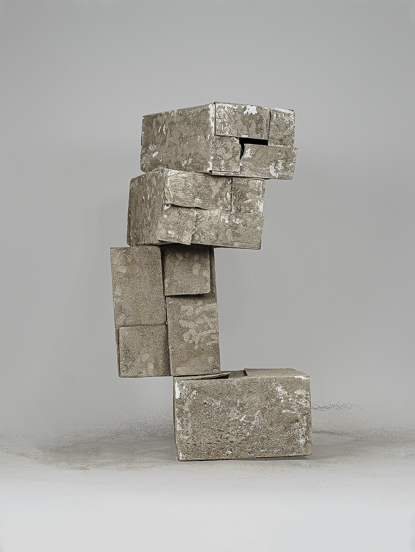 Photographie de Michel Rey prise de face. Elle représente 4 cartons usagés, peints avec de la cendre. Ils sont agencées en équilibre instable ett empilés en V les uns sur les autres.