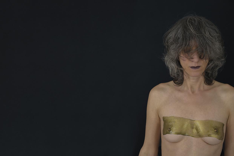 Photographie de Michel Rey - Portrait d'une femme en plan américain, nue de face, les yeux fermés, les bras tombants. Un rectangle de peinture dorée barre sa poitrine.