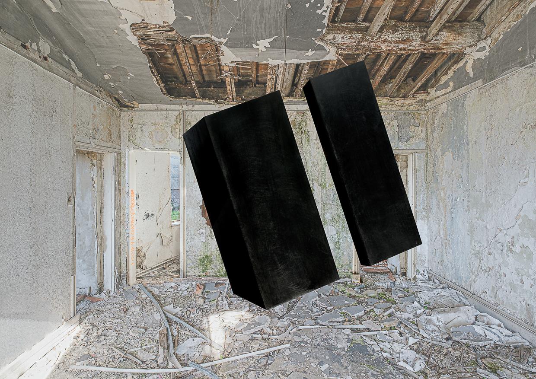 Photographie de Michel Rey prise dans le chateau de la La Gafette à Port de Bouc. La photo représente un cube noir,divisé en 2 parties, en suspension dans une des pièces du chateau . Les murs de la pièce sont constitués de 3 collages supperposés de différentes parties de la même salle.