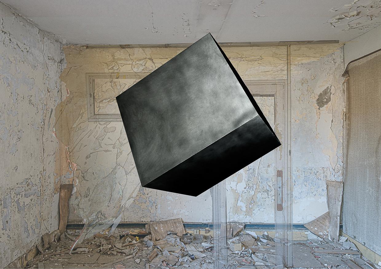 Photographie de Michel Rey prise dans le chateau de la La Gafette à Port de Bouc. La photo représente un cube noir en suspension dans une des pièces du chateau . Les murs de la pièce sont constitués de 3 collages supperposés de différentes parties de la même salle.