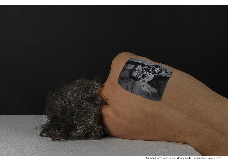 Photographie de Michel Rey - Portrait d'une femme dos nue couchée couchée sur une table blanche avec une photo de sa gran-mère collée sur son omoplate. Intitulé de la photo : Ma grand-mère, vend du linge de maison dans sa boutique jusqu'en 1942