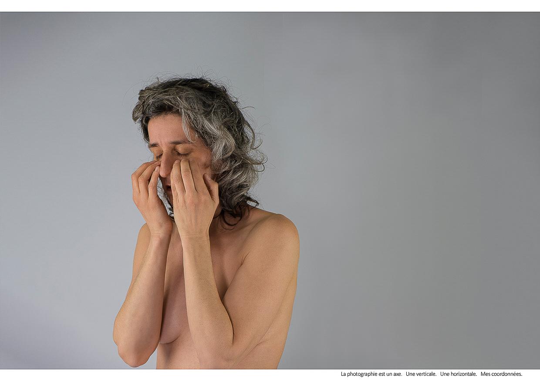 Photographie de Michel Rey - Portrait d'une femme (plan américain), nue,, assise. Son visage est entre ses deux mains Les yeux sont fermés. Intitulé de la photo : La photographie est un axe. Une verticale. Une horizontale. Mes coordonnées.