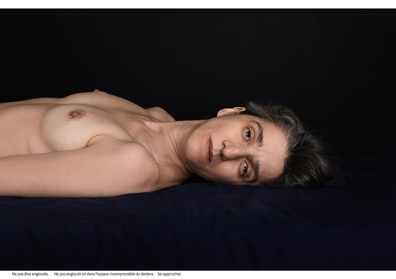 Photographie de Michel Rey - Portrait d'une femme (plan américain), nue,, couchée sur un lit, la tête tourné vers le spectateur les yeux ouverts fixant le spectateur. Intitulé de la photo : Ne pas être engloutie. Ne pas engloutir et dans l'espace incompressible du dedans, Se rapprocher.