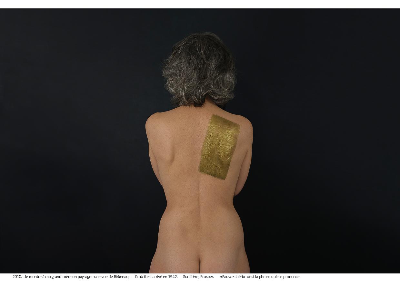 Photographie de Michel Rey - Portrait d'une femme nue de dos, les bras croisés la tête tournés vers l'arrière-plan noir. Un rectangle de peinture dorée barre son omoplate. Intitulé de la photo : 2010 je montre à ma grand-mère un paysage : une vue de Birkenau, là où il est arrivé en 1942. Son frère, Prosper. «Pauvre chéri» c'est la phrase qu'elle prononce.