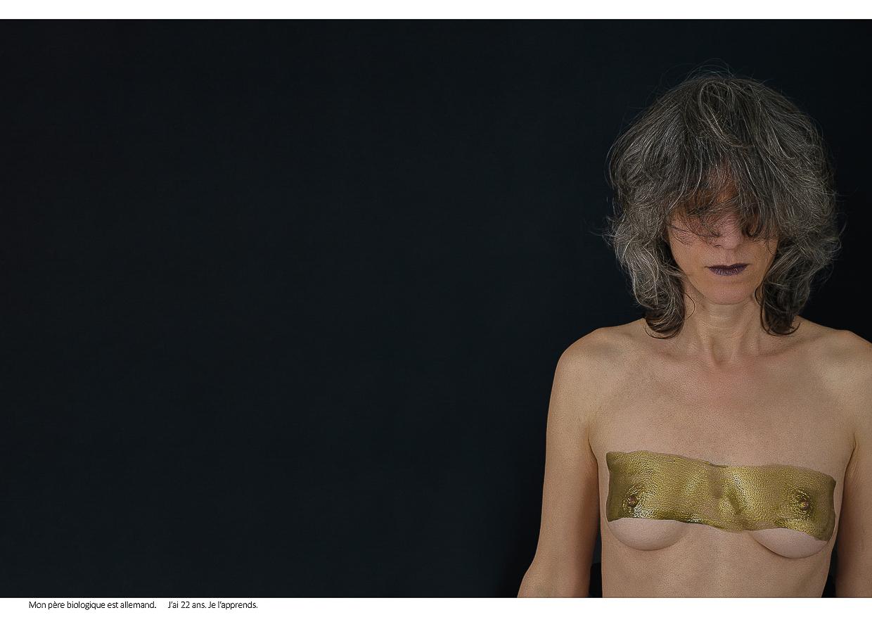 Photographie de Michel Rey - Portrait d'une femme en plan américain, nue de face, les yeux fermés, les bras tombants. Un rectangle de peinture dorée barre sa poitrine. Intitulé de la photo : Mon père biologique est allemand. J'ai 22 ans. Je l'apprends.