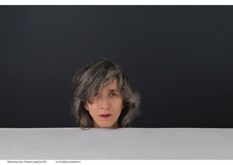 Photographie de Michel Rey - Portrait d'une femme le menton au dessus d'une table blanche avec un fond noir en arrière-plan, Les yeux fixent le spectateur. Intitulé de la photo : Faire le pari de « l'Ouvert » jusqu'à la fin. Le 15 août je rencontre C.